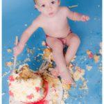boy sat in cake mess after cake smash