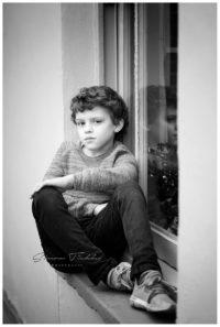 child portrait on window ledge at winter in mansfield, nottingham