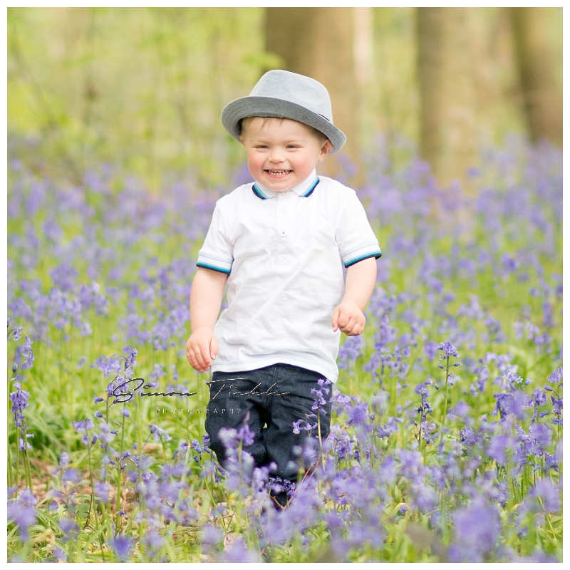 boy wearing hat wanders in bluebells - child photo shoot nottingham